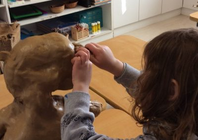 Photo of a child making a clay sculpture